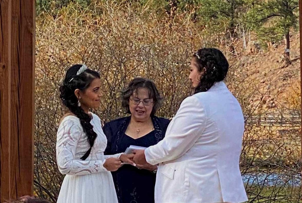 Two brides, holding hands, before the officiant in an out-door autumn setting.